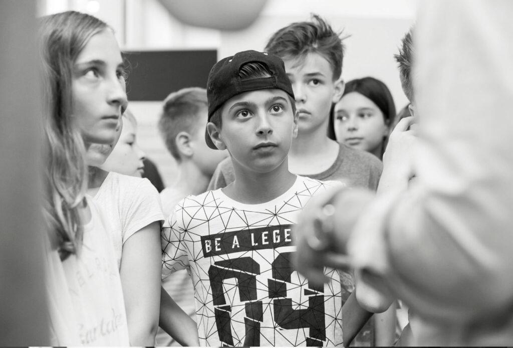 Eine Gruppe Schüler, die einer Person außerhalb des Bildausschnitts zuhört