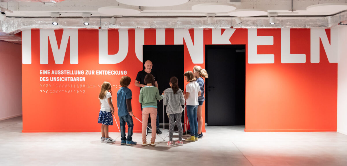 The museum entrance with a group of children standing around a blind man
