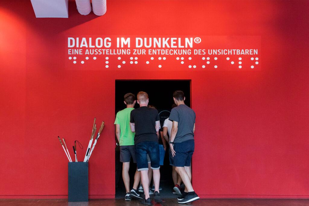 """Gruppe betritt Eingang in die Ausstellung """"Dialog im Dunkeln"""" mit einer Gruppe Besucher*innen"""