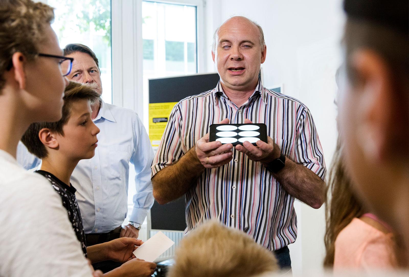 Workshop-Leiter mit Smartphone vor Gruppe erklärend