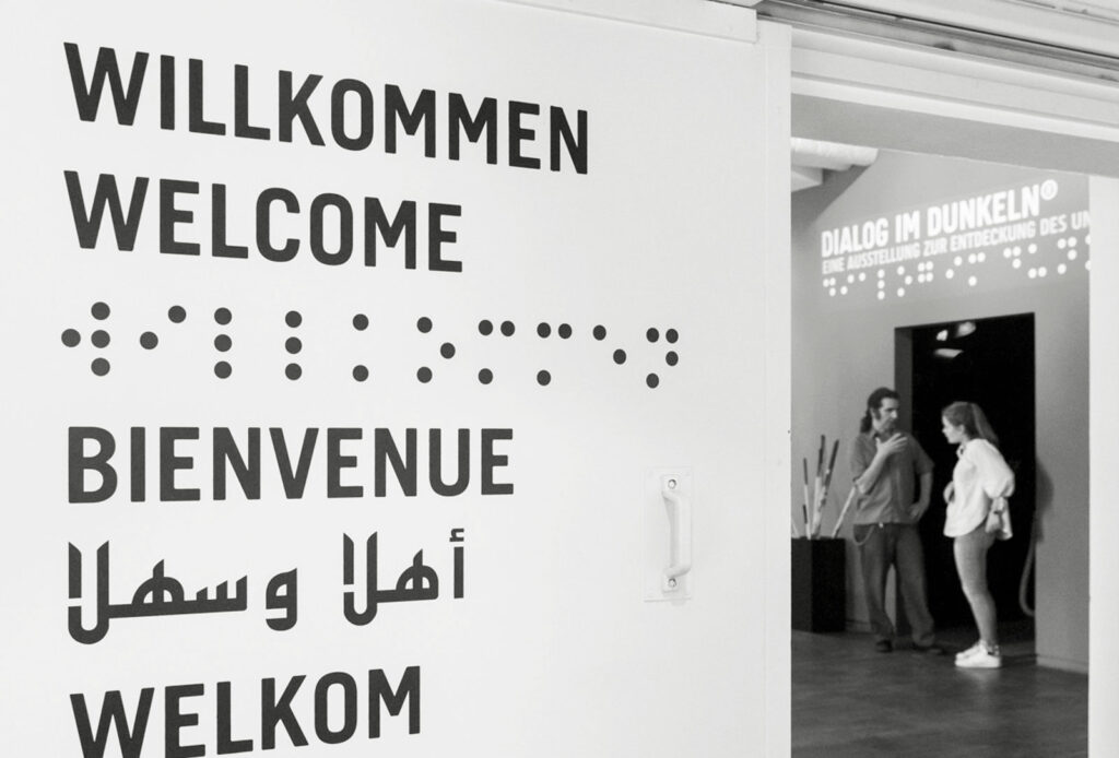 Detailansicht des Eingangs zur Ausstellung und Willkommensschriftzug in verschiedenen Sprachen