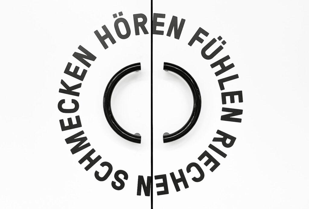 Detail Türgriff mit kreisförmiger Beschriftung: Hören Fühlen Schmecken Riechen