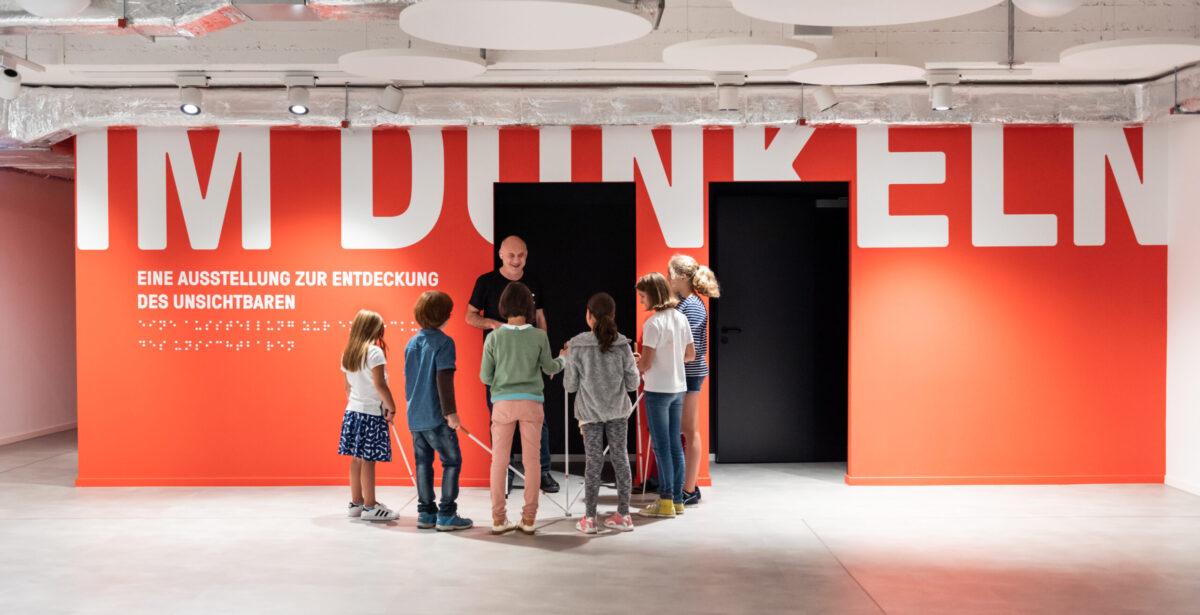 """Blick in das Foyer mit einer roten Wand mit der Aufschrift: """"IM DUNKELN"""" in weißen Letter. Davor steht eine Gruppe von Kindern die um einen blinden Mann stehen."""